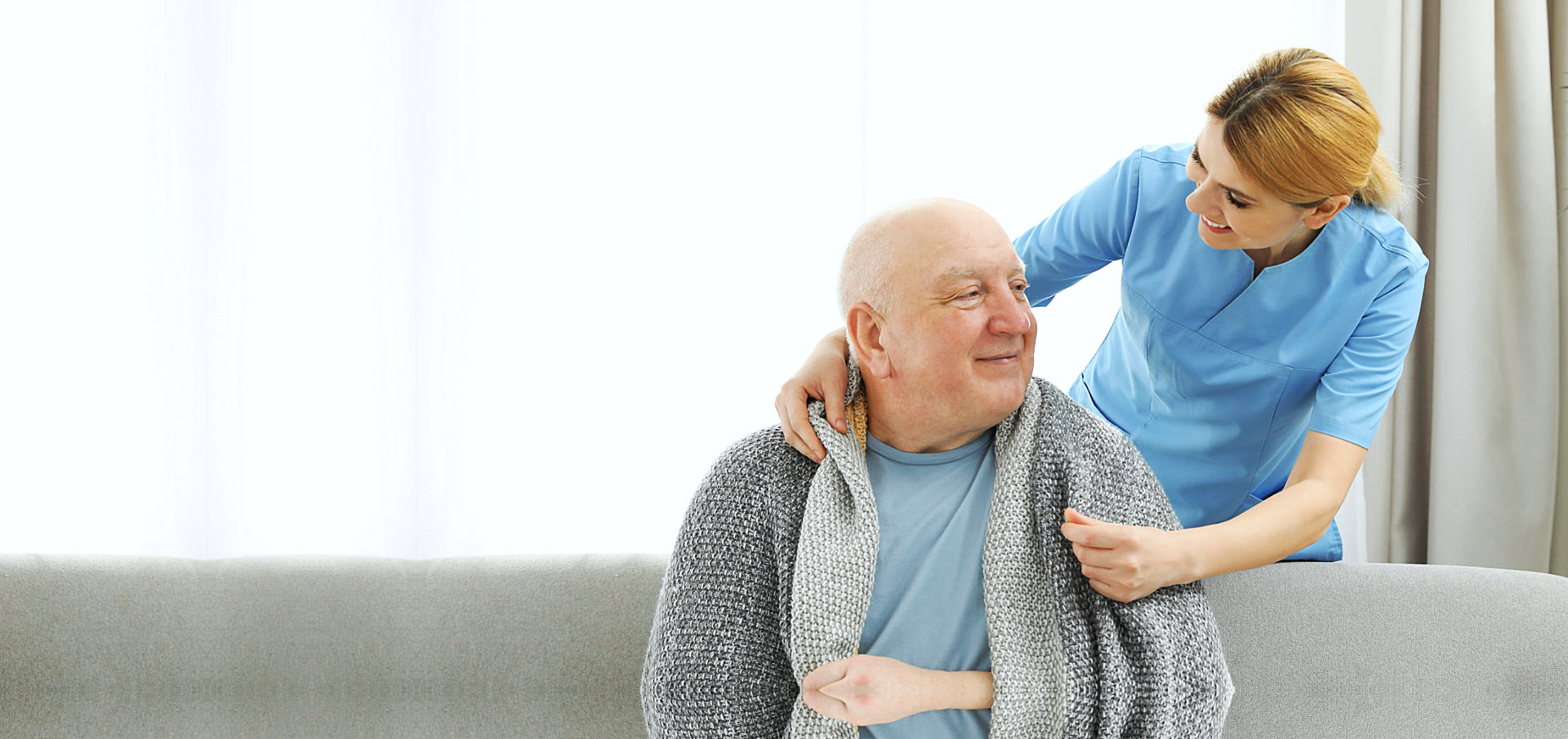 caregiver putting a blanket on a senior man