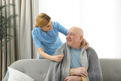 nurse covering elderly man with blanket